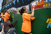 Volunteers and students  paint a mural against bullying at a middle school in the Richmond Hill neighborhood in the borough of Queens in New York on Friday, August 13, 2010  (© Frances M. Roberts)