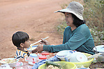 A mother helps her small son eat breakfast at a restaurant along the roadside in the Cambodian village of Talom.