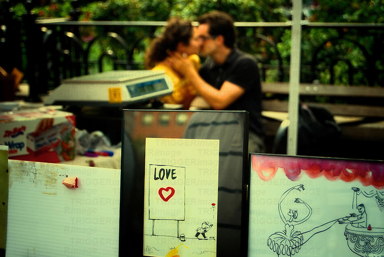 A couple kissing in the background with artistic drawings about love in the foreground. Union Square, Manhattan, New York City.