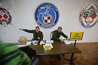 "Privates Piotr Kolcz and Konrad Kosiol sit at the reception desk for new conscripts under a sign that reads ""Air Force"". This year's class of drafted recruits is the final one after 90 years of compulsory military service, as Poland's army turns professional in 2009."