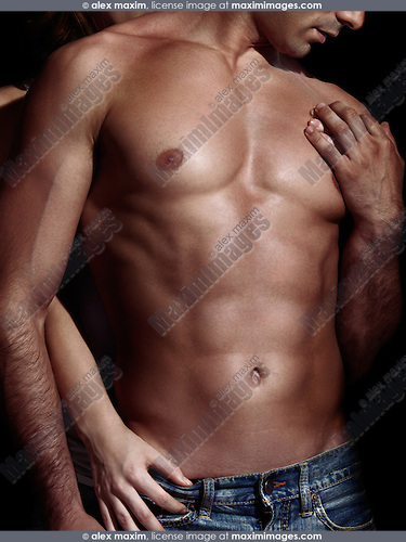 Closeup up of a woman standing behind a man with muscular bare torso dramatic sexy couple photo isolated on black background.