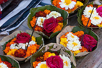 India, Rishikesh.  Leaf-baskets of marigolds and roses for sale to worshippers.  A candle will be lighted in the basket which will then be set into the Ganges (Ganga) River.