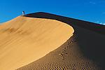 A traditional dressed moroccan man walks up a sand dune, Sahara desert, Morocco.