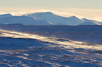 Wind blowing snow over the arctic tundra with the Philip Smith Mountains of the Brooks range in the distance.