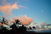 At sunset, a rainbow meets the moon over Kukuiula Harbor in Poipu, Kauai.