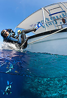 RH0393-D. Split over-under view of female scuba diver (model released) backrolling from boat into ocean overtop coral reef. Palau, Pacific Ocean.<br /> Photo Copyright &copy; Brandon Cole. All rights reserved worldwide.  www.brandoncole.com
