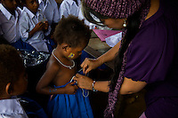 One of the 'Twin Teachers',  Rossy, helps a playgroup student from the Papua branch of Kartini Emergency School put on her new school uniform. Utilising local volunteer teachers, the twins have opened similar small scale schools in other parts of Indonesia which they visit regularly. Since the early 1990s, twin sisters Sri Rosyati (known as Rossy) and Sri Irianingsih (known as Rian) have used their family inheritance to set up and run 64 schools in different parts of Indonesia, providing primary education combined with practical skills to some of the country's most deprived children.