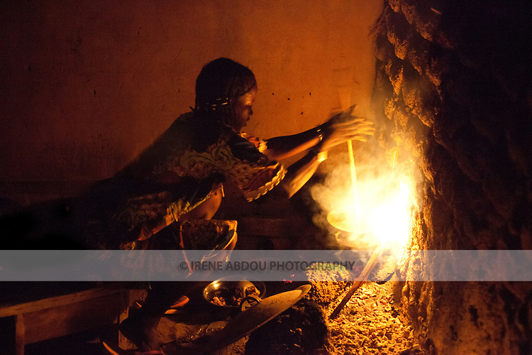 """A woman in Djibo, Burkina Faso rolls a spatula between her hands to cook millet """"pot,"""" similar to the Italian polenta.  Without a stove or electricity, women throughout West Africa cook outside on an open fire."""