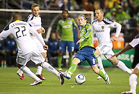Seattle Sounders FC midfielder Erik Friberg passes the ball in front of L.A. Galaxy defender Leonardo while forward Chad Barrett follows during play at Qwest Field in Seattle Tuesday March 15, 2011. The Galaxy won the game 1-0.