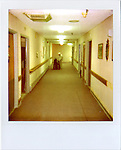 Hallway scene.  Douglas Care Center...Alzheimers.  Douglas, Wyoming..Mike Eberspecher was diagnosed at 60 with early onset Alzheimers.  The disease, a subset of dimentia, gradually impairs the brain's ability to form new memories, simultaneously undoing connections that make up old memories.  Patients generally experience memory loss from the present, backwards.  Early onset Alzheimers tends to progress quicker in younger patients. ..Carolyn Eberspecher has been caring for her husband, Mike, for the last five years.  Over time, he has gradually lost his ability to care for himself and relies on her for most of his needs.  In April of 2010, Carolyn will place her husband in an Alzheimer's care unit in the town's nursing home.  .Carolyn Eberspecher attends church in Douglas, Wyoming.  Carolyn and Mike attend separate churches.  After Mike was diagnosed with Alzheimers, he returned to attending Mormon church, a tradition which had fallen by the wayside for most of his adult life.