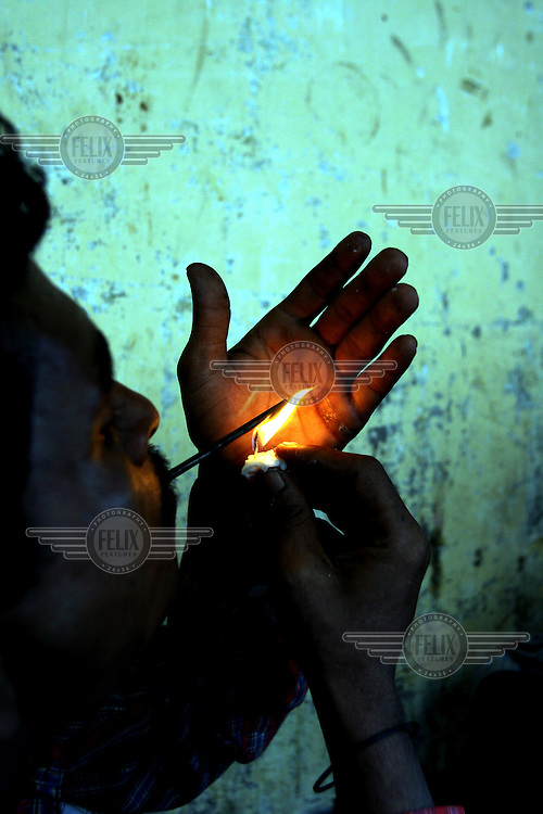 A drug addict from a slum community smoking heroin.