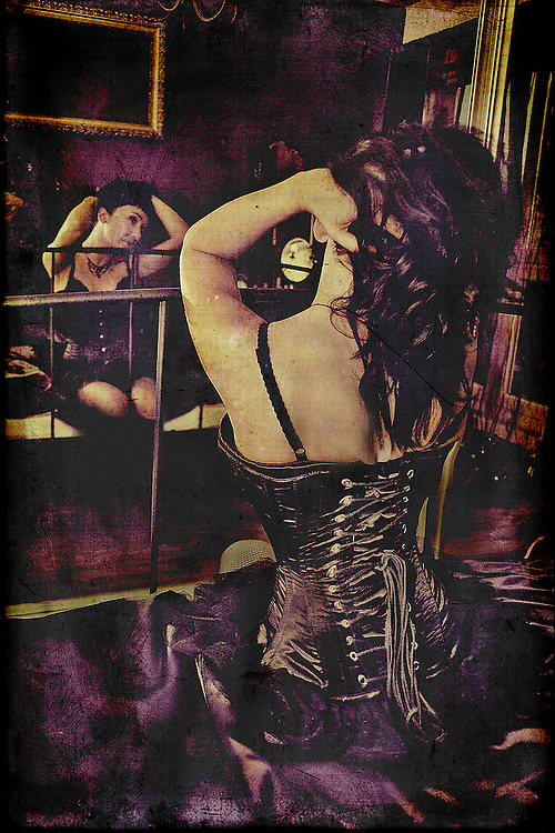 A woman in a black vintage corset, siting on the bed , with hands in her dark hair, opposite the big mirror