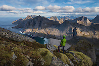 Female hiker takes in view over Bunes beach while hiking to Storskiva mountain peak, Moskenesøy, Lofoten Islands, Norway