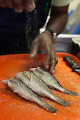 Copyright Justin Cook | September 26, 2013 - Ricky Moore prepares fresh croaker for frying at Saltbox Seafood Joint.