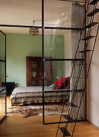 This glass wall frames and encloses the bedroom as well as flooding the room with light