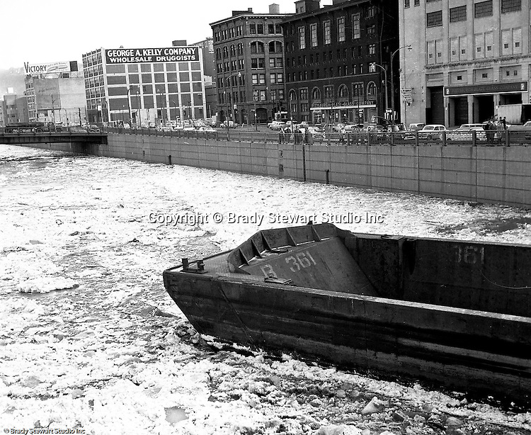 Pittsburgh PA:  High waters on the Allegheny River after a snow melt - 1959.  View of the water covering the 10th Street bypass and a barge stuck under the 6th street bridge
