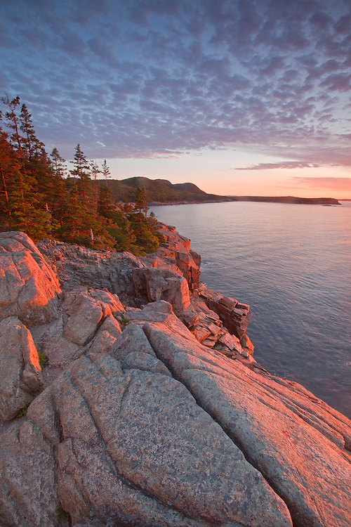 View of the granite Otter Cliffs from Otter Point with Gorham Mountain and the Beehive in the distance at Acadia National Park, Maine, USA