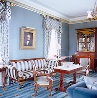 In the living room, tasselled brocade curtains hang on either side of a Victorian portrait which hangs above  a sofa, re-upholstered in a striped satin, part of a set of antique walnut furniture