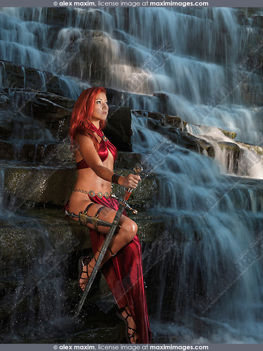Beautiful woman fantasy warrior sitting on a rock amidst of a waterfall cascade
