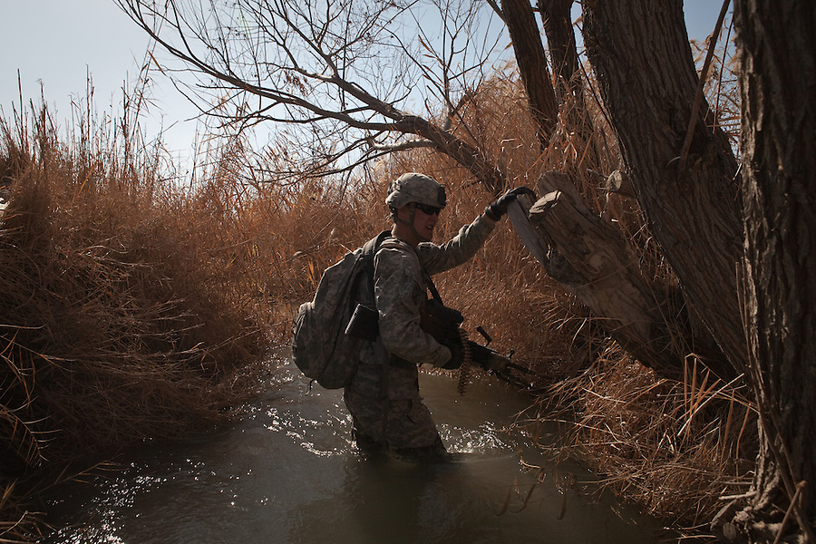 SPC Timothy Eickmeier with Charlie Co. 1st Battalion 12th Infantry Regiment, 4th Infantry Division slogs his way through an irrigation canal during a patrol in Zhari District, Kandahar, Afghanistan. The violently contested district sits astride the strategically Highway 1 ringroad between Kandahar and Lashkar Gah and is seen by some as the birthplace of the Taliban movement.