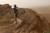 PFC Clifford Kaja, 21 of Baldwin, MI of Team Gator, a combined force of 1-32 Calvary, treads carefully over a rock outcropping while looking for IED and weapons caches near Muqdadiyah, Iraq.