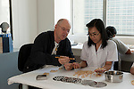 Jacques Branellec, owner of Jewelmer interacts with a pearl worker