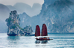 Vietnam's Halong Bay is one of the most dramatic landscapes in all of southeast Asia.  Karst mountains and rocky pinnacles rise dramatically out of the bay.  The unusual shape of the sails of the fishing craft complete the monochromatic scene.