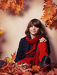 Smiling boy wearing trendy fall clothes, blue jacket with red pants and scarf, sitting on fallen red leaves, autumn childrens fashion