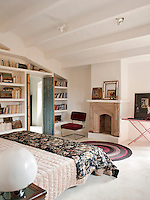 The bedroom has striking architectural features of a vaulted ceiling and fireplace