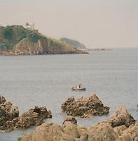A small fishing boat in the ocean at Playa de Silencio, Asturias, Spain