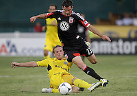 WASHINGTON, DC - AUGUST 4, 2012:  Chris Pontius (13) of DC United is slide tackled by Chris Birchall (8) of the Columbus Crew during an MLS match at RFK Stadium in Washington DC on August 4. United won 1-0.
