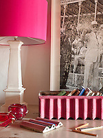 Detail of the hall table with a lamp with a hot pink shade and a framed black and white vintage photograph