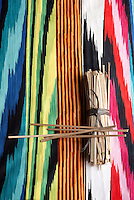 A length of graphic multi-coloured fabric from Missoni Home is juxtaposed with a bundle of sticks