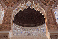 Polychrome mocarabe work and square columns with carved floral decoration and Arabic script, around a wooden coffered ceiling in the Court of the Lions, built 1362 in the second reign of Muhammad V, in the Nasrid dynasty Palace of the Lions, Alhambra Palace, Granada, Andalusia, Southern Spain. The Alhambra was begun in the 11th century as a castle, and in the 13th and 14th centuries served as the royal palace of the Nasrid sultans. The huge complex contains the Alcazaba, Nasrid palaces, gardens and Generalife. Picture by Manuel Cohen