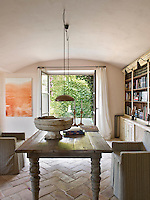 The dining table is situated directly opposite French windows that open onto the courtyard garden