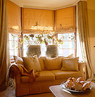 A comfortable sofa occupies the bay window in the living room
