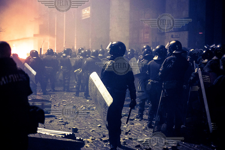Riot police officers with shields and helmets gather near Maidan Nezalezhnosti (Independence Square), renamed EuroMaidan by protesters since November 2013. Protests against the government of President Viktor Yanukovych were sparked on 21 November 2014 by the Ukrainian government's decision to suspend preparations for the signing of an association agreement with the European Union that would have increased trade with the EU. Some believe that the U-turn came about as a result of pressure from President Putin of Russia who wants Ukraine to join a customs union with itself, Kazakhstan and Belarus. Russia offered 15 billion dollars of soft loans and reduced price gas to Ukraine at the same time as discussions with the EU were taking place. After weeks of protests and a number of deaths, Prime Minister Mykola Azarov and the entire cabinet resigned. Protesters are holding out, however, for President Yanukovych to resign and continue to occupy public buildings and squares to put pressure on the president. On 18 February, after Yanukovych's party scuppered a move to change the constitution to reduce the powers of the president, renewed fighting between protesters and police broke out and had cost the lives of around 80 people by Friday 21st February.