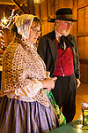 Old Bethpage, New York, USA. Decemer 26, 2014. Wife SHERRI GUTHRIE and husband CHART GUTHRIE, dressed in traditional 19th Century clothing, visit a booth inside the Barn, at night, on the historic, rustic grounds of Old Bethpage Village Restoration, transformed by candlelight and Christmas decorations into a Nineteenth Century holiday experience for Long Island visitors. Candlelight Evenings are held until December 30th.