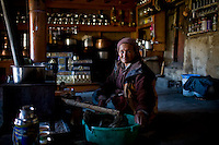 Tsering Dolma, a friend of the family prepares breakfast in the 200 year old kitchen of Rinchen's house on 2nd June 2009. They run a home stay program in Ulley Valley, a scattered village of only 5 houses, one school, 38 people, 4 school children, and 4 pet dogs. The village is not accessible by road. The homestay program is managed by 'Snow Leopard Conservation Organisation', an NGO that helps families in the mountains that face constant snow leopard attacks on their live stock. Leh town is 3505m above sea level, in the Indian Himalayan mountains, in the region of Ladakh, located in the Indian Himalayas, in the northern state of Jammu and Kashmir. Photo by Suzanne Lee