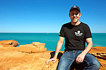 "Jeff Hansen Director of Sea Shepherd Australia, sitting on the rocks at Gantheaume Beach, while the ""Steve Irwin' in the background, is on it's way to the port in Broome"