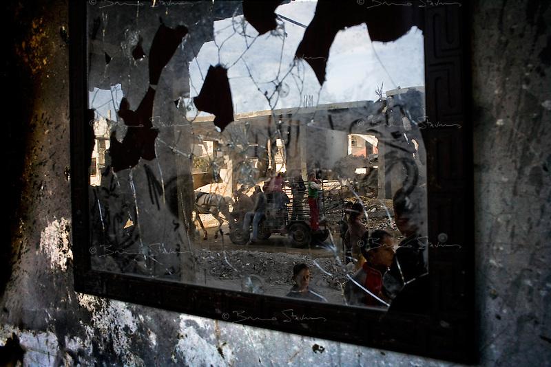 Rafah, Gaza Strip, Jan 15 2009.Children play near buildings damaged during an Israeli airstrike..
