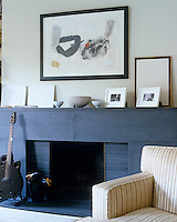 A large fireplace constructed from steel and black stone is a welcoming focal point in the living room of a Manhattan apartment