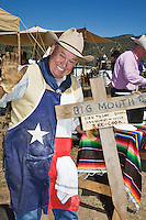The 21st annual Lincoln County Cowboy Symposium was held in October 2010 at the Ruidoso Downs Racetrack in Ruidoso, New Mexico. Wayne Calk of the Calk-Clark chuckwagon out of El Paso, Texas, poses with his sign.