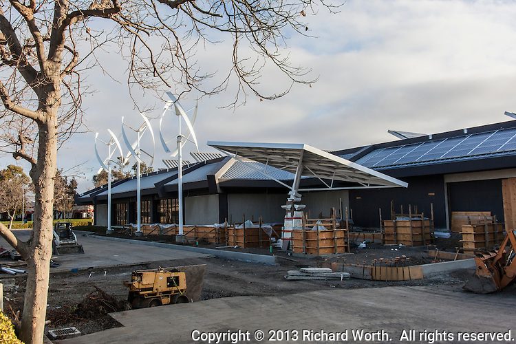 Wind turbines, a solar tracking tree and roof mounted solar panels at the Zero Net Energy Center under construction in San Leandro, California.