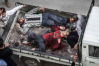 In this Tuesday, Oct. 23, 2012 photo. Syrian civilians lay down at the back of a truck as they arrive to one hospital in Tarik Al-Bab after got injured by mortar shelling while they were buying bread at one bakery in Hananu district, at the northeast of Aleppo City. (AP Photo/Narciso Contreras).