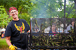 The Portland Farmers' Market in the South Park Blocks on Saturday mornings. Freshly roasted peppers fills the air with smokey aroma.  Customers can buy different types of freshly roasted peppers grown by Phil and Liz Smith from their farm West Wind Gardens located just outside Portland in Forest Grove, Oregon. Pictured here is friend Charles Kralove roasting a fresh batch of chilis.