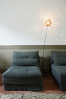 Situated between two daybeds in the living room a floor lamp with an etched glass shade casts calligraphic reflections on the white wall behind