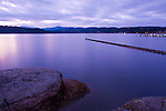 Idaho, Coeur d' Alene. The breakwater on Lake Coeur d' Alene  and lakeshore rocks on Tubbs Hill in the lavender light of dusk.