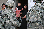 An Iraqi woman pleads with U.S. soldiers not to arrest her husband as a during a clearing operation south of Mahmudiyah, Iraq. The man's name was not on the U.S. list of suspected insurgents, but Iraqi troops insisted that he was a militant and took him into custody. As the man was led away, the younger woman followed the soldiers and hurled curses at them. July 11, 2007. DREW BROWN/STARS AND STRIPES