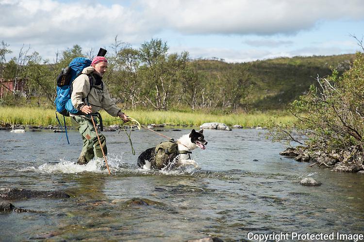 Mann og kløvhund krysser elv. ---- Man and pack dog crossing river.